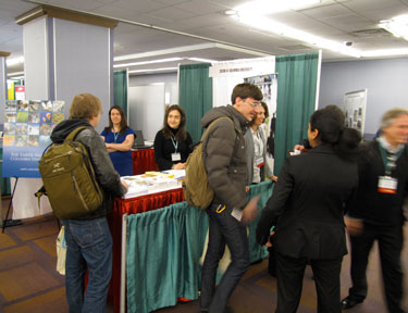 Photo of CIESIN booth at AAG 2012 conference shows booth workers and attendees.