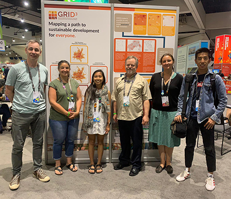 CIESIN staff members exhibiting a display graphic describing the goals of the GRID3 program, at the Sustainable World Showcase of the 2019 Esri User Conference.
